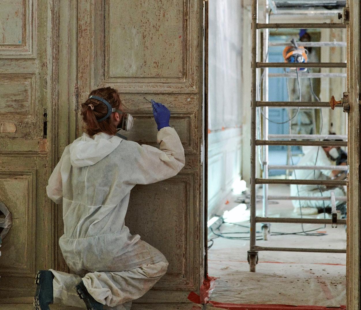 Une restauratrice en plein travail de dégagement des couches de peintures ajoutées après le XVIIIe siècle